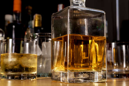 Square glass bottle of scotch on the wooden bar