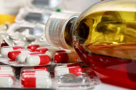 Botella de linctus al lado de cápsulas y píldoras. Medicamentos vencidos Foto de archivo
