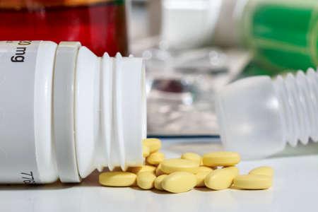 Pequeñas píldoras amarillas salen de una botella de plástico volteada, frente a otros medicamentos Foto de archivo