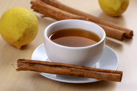 lose up: Cup and saucer of Chinese Pu-erh tea, with cinnamon sticks and lemons, on wooden table