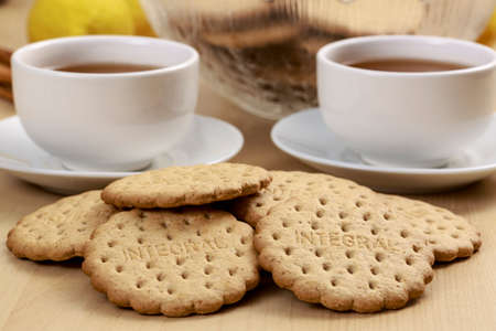 lose up: Low-calorie cookies in front of Pu-erh tea cups, ideal afternoon meal to lose weight. Word integral that can be read in biscuits refers to kind of cookies  (whole-grain crackers), not a trademark