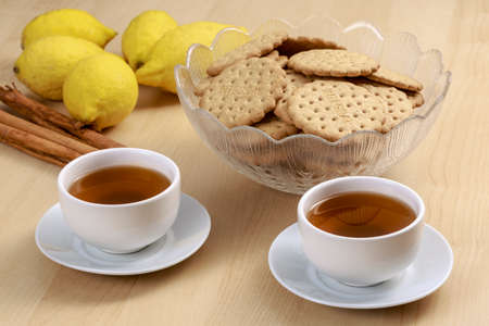 Pu-erh tea cups beside a bowl with cookies, cinnamon sticks and lemons. The word integral that can be read in the biscuits refers to a kind of cookies  (whole-grain crackers), not a trademark
