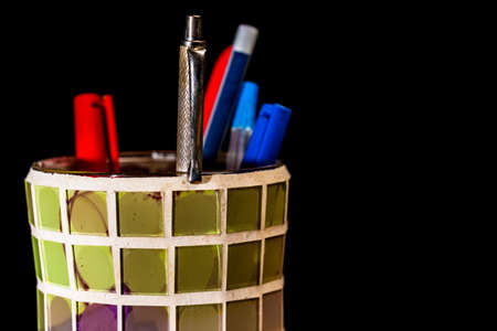 Close-up of colorful crystal pencil holder with pens, pencils and marking pens on black background Stock Photo