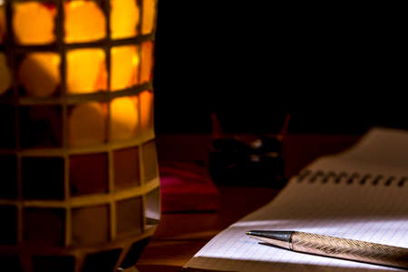 Pen over a graph notebook, beside a crystal pencil holder of different colors. Chiaroscuro