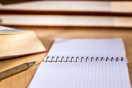 Graph notebook over a wooden desk, beside a metal pen and books Stock Photo