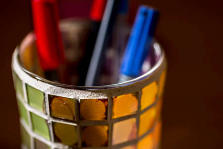 Close-up of colorful pencil holder made of crystal squares of different colors