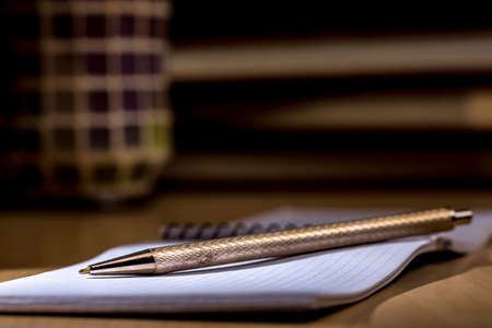Pen and small notepad over a desk. Chiaroscuro Stock Photo