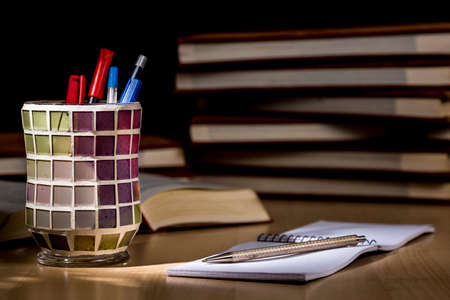 Desk with pens, graph notebook, colorful pen holder and piles of books. Chiaroscuro Stock Photo