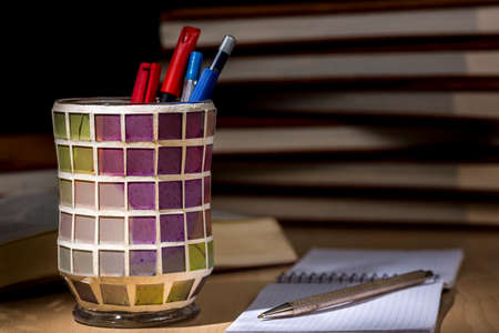 Close-up of metal pen over a graph notebook, beside a colorful pen holder. Piles of books at dark background. Chiaroscuro Stock Photo