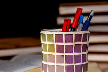 Detail of a colorful pencil holder made of crystal squares of different colors, in front of piles of books