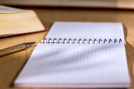 Small notepad over a wooden desk, beside a metal pen and books Stock Photo