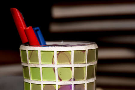 Close-up of colorful pencil holder made of crystal squares of different colors, in front of piles of books Stock Photo