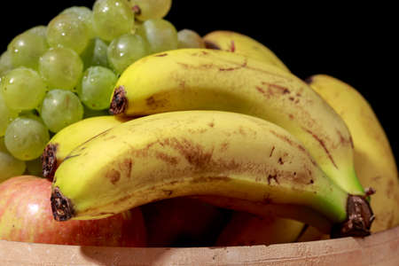 afters: Bananas into a ceramics bowl, beside other fruits as apples and grapes, on black
