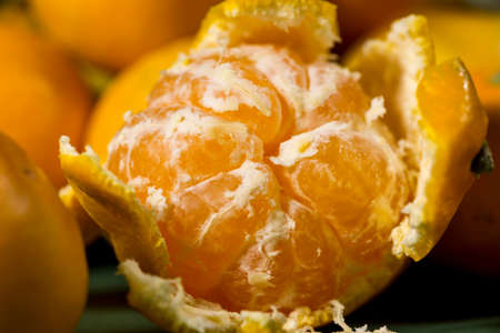 vesicles: Close-up of half peeled orange tangerine between other citrus fruits Stock Photo