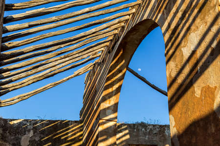 Detail of wooden beams and archway in load-bearing wall of ancient roofless building, with blue sky and daymoon at background