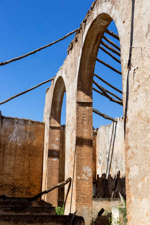 Arched bearing wall of ancient roofless building. Abandon house under the blue sky