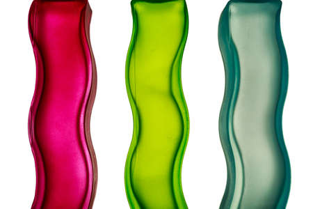 Sinuous glass columns of different colors on white. Bright primary colors background. Stock Photo