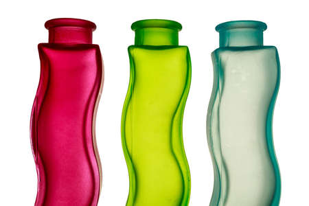 Colorful decorative glass jars with sinuous shape on white background. Primary colors of light