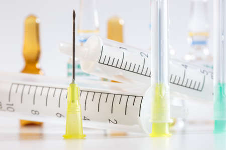 Needles and syringes in front of ampules of drugs. Intravenous medicines on white Stock Photo