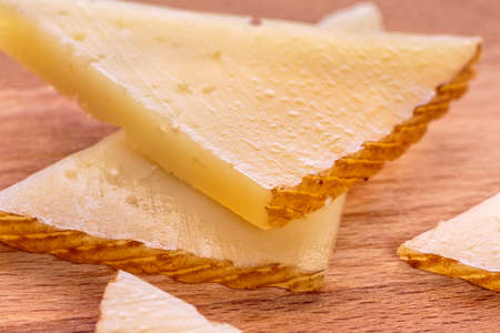 vacas lecheras: Spanish tapas. Slices of Manchego curado cheese over a wooden table Foto de archivo