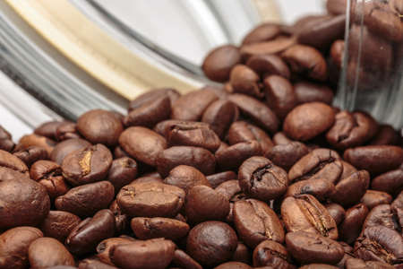 Coffee beans get out of overturned glass jar Stock Photo