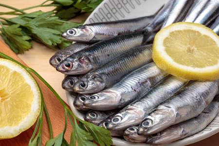Fresh anchovies beside parsley and lemon slices. Fishery of Mediterranean diet