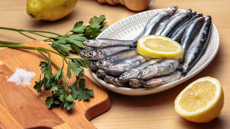 Oval dish with raw anchovies, beside parsley, salt and lemons. Mediterranean diet