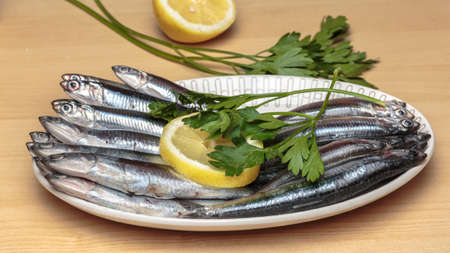 Oval dish full of raw anchovies with lemon slices and parsley over a wooden table. Mediterranean diet