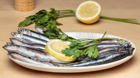 Oval dish full of fresh Mediterranean anchovies, known as boquerones in Andalusian gastronomy, beside parsley and lemon slices. Mediterranean diet