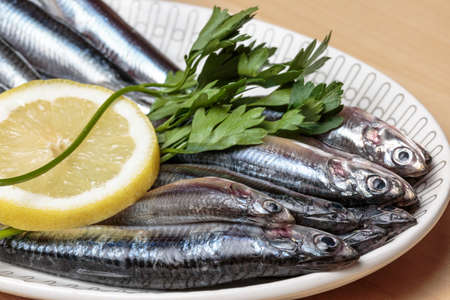 Raw seafood. Fresh anchovies with parsley and lemon slice. Healthy food