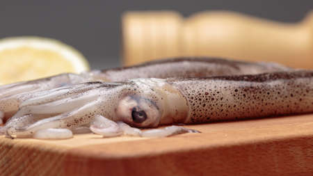 Detail view of raw squid that is over a wooden cutting board Stockfoto