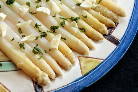 White asparagus seasoned with garlic and parsley, plated in a decorated ceramic dish, on black. Fresh and healthy food
