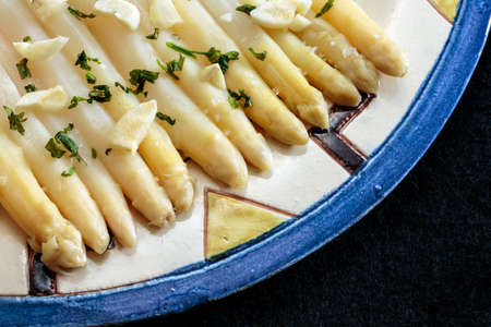 Asparagus seasoned with garlic and parsley, plated in a decorated ceramic dish, on black. Fresh and healthy food Stockfoto