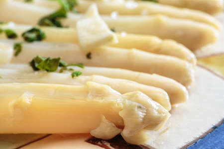 Detail of white asparagus seasoned with garlic and parsley, over a decorated ceramic dish. Tasteful and healthy food Stock Photo