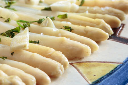Close-up of tips of white asparagus seasoned with garlic and parsley, plated in a decorated ceramic dish. Fresh and healthy food Stockfoto