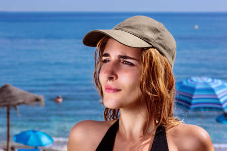 Young woman at beach, summertime. Close-up of pretty girl with nose ring and wet hair under the sun, in front of parasols and the blue sea. She wears a green baseball cap and a black swimsuit Stockfoto