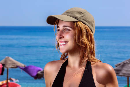 Beautiful smiling woman at beach. Close-up of happy girl with green baseball cap and black swimsuit in front of sunshades and the blue sea. Her blonde hair is wet and has a nose ring. Summer scene