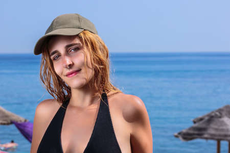 Seductive girl at beach. Close-up of pretty young woman with nose ring and wet hair under the sun, in front of parasols and the blue sea. She wears a green baseball cap and a black swimsuit Stockfoto