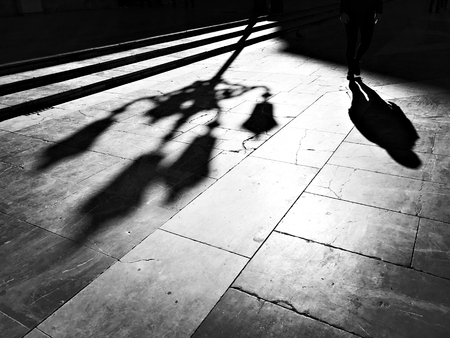 Backlight and silhouettes of a person and a lamppost on the ground of a city square
