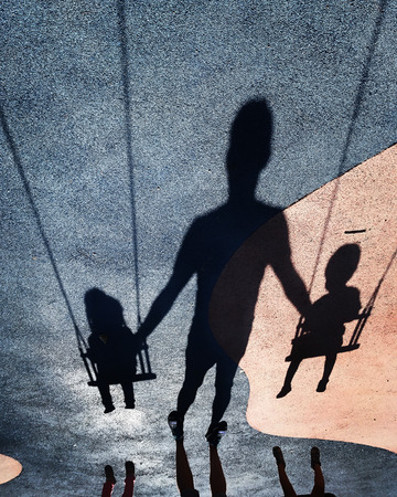 Image upside down of shadows on the floor of an adult swinging two children in the park