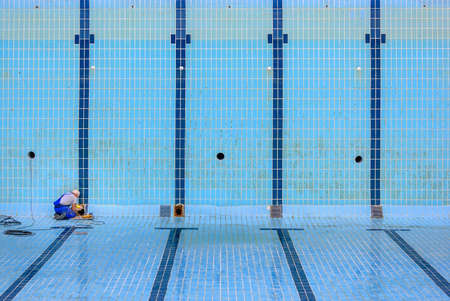 a worker doing some maintenance work in a swimming pool