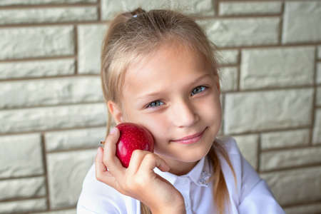 Portrait of a pretty tired girl who is holding a red apple. Healthy food and lunch for school children. The concept of hard and difficult education at school, a large number of homework tasks