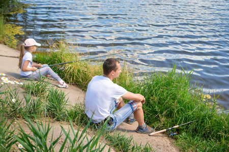 Father with daughter sit on the shore of lake with fishing rods and catch fish. Concept of outdoor holiday and vacation with a family. Father spends time with his child and teaches her to catch a fish