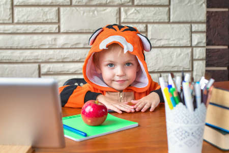 Portrait of a cute little boy who is sitting at a table with books, pencils, tablet, notebook and red apple for lunch. Preparing for school for preschoolers. Online and home education