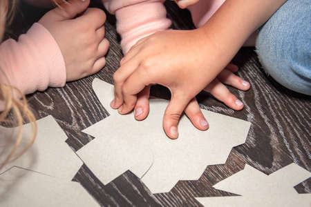 Children solve the puzzle and try to put together the pieces of the carton with symbols on the brown wooden floor. Kid's game on holiday. Close-up of young hands collecting a riddle.