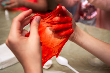The child makes a bright red transparent home hand made slime and plays with it. The kids having fun and being creative by science experiment with the creation of a stretching toy called a slime.