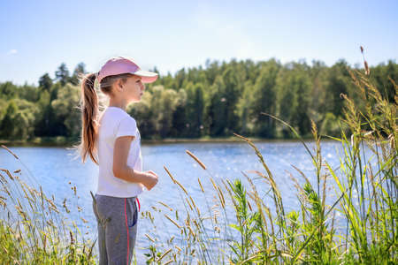 A girl with long blonde hair tied in a ponytail, wearing a t-shirt and a pink cap stands on the bank of the river and looks into the distance. Concept of time in nature and outdoors. Summer holidays Stock Photo