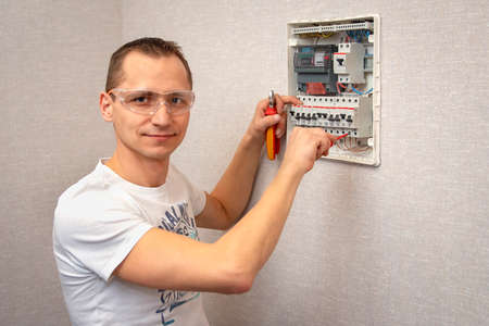 Portrait of a young man in a white t-shirt and protective glasses who works as an electrician and stands near an electrical fuse board. The concept of the safety of residential electrical systems.