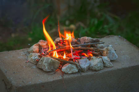 Small burning fire on a stone slab. Concept of tourism, camping, gatherings around the campfire at night with friends and marshmallows, watch the fire, sing songs to the guitar, relax from the city