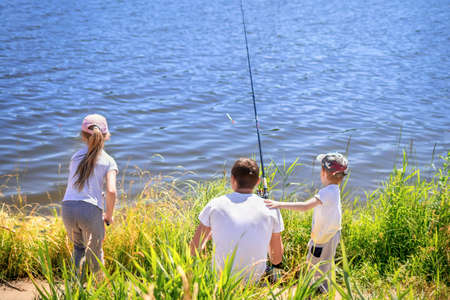 Father with daughter and son sit on the shore of the lake with rods and catch fish. Concept of outdoor recreation and holiday with family and fishing. Man teaches his children to catch a fish.